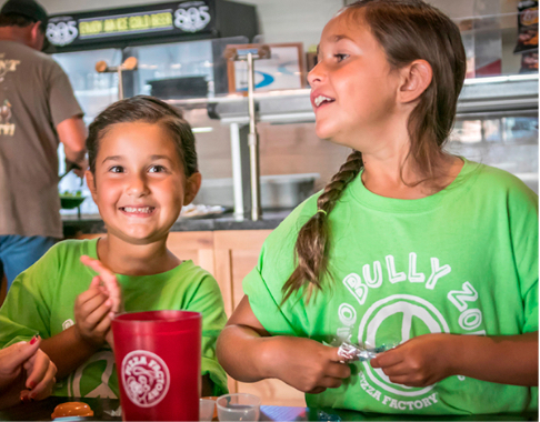Children at Pizza Factory with green No Bully Zone Peace Sign Logo shirts
